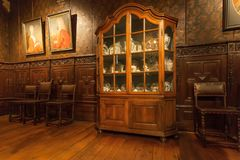 Porcelain set on shelves of antique cupboard in printing museum of Plantin-Moretus, UNESCO World Heritage Site. ANTWERP, BELGIUM - MAR 30: Porcelain set on royalty free stock images