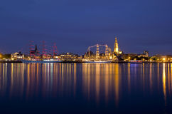 Antwerp's Tall Ship Race by night. Antwerp Tall Ships Race, two three-master ships are moored at the river Scheldt, with the cityscape of Antwerp in the Stock Photography