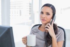 Antwortendes Telefon ernsten Sekretärs und trinkender Kaffee Lizenzfreie Stockfotografie