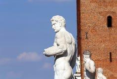 Antyczna marmurowa biała statua i duży wierza w tle Zdjęcia Royalty Free