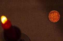 Antyczna srebna moneta i płonąca świeczka zdjęcie stock