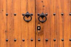 Antyczna zamknięta drewniana brama z dwa drzwiowego knocker pierścionkami Fotografia Stock