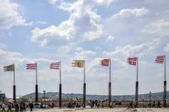 Antyczne flagi trzepocze w wiatrze na tle błękitny chmurny niebo fotografia stock