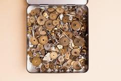 Antyczne przekładnie inkasowe w rozpieczętowanym metalu pudełku makro-, beżu papierowy tło Płytka głębia pole, miękka ostrość szk Zdjęcie Royalty Free