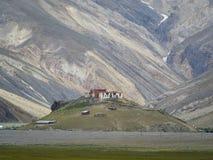 Antyczny Buddyjski monaster Rangdum stojaki na wzgórzu zakrywającym z zieloną trawą przeciw tłu skała z skały cr Zdjęcia Stock