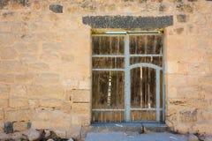 Antyczny drewniany drzwiowy ustawiający w kamiennej ścianie Zdjęcie Stock