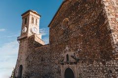 antyczny kamienny kościół z zegarowy wierza przy starym europejskim miastem, Cannes, Francja obraz stock