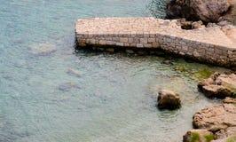 Antyczny kamienny ponton przy turkusu jasnego wody dennym brzeg Obrazy Royalty Free