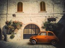 Antyczny mały pomarańczowy Włoski samochód, parkujący na drodze przed antycznym mieszkaniem zdjęcia stock