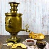 Antyczny miedziany samowar na drewnianym stole z filiżanką herbaciani breadcrumbs ciastka przyskrzynia obraz stock