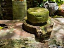 Antyczny millstone zielonego liszaju wokoło i Antyczny millstone stawia na starych drewnianych deskach Za tylnymi zielonymi drzew Fotografia Stock