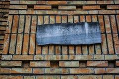 Antyczny pomnik z romanian pisaniami, pomarańczowy ściana z cegieł Zdjęcia Stock