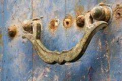 Antyczny rdzewiejący drzwiowy knocker na drzwi z zatartą błękitną farbą Obraz Royalty Free