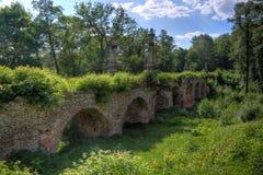 Antyczny rujnujący przerastający czerwonej cegły most w lesie obrazy stock