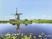 Antyczny wiatrowy młyn odbijał w błękitnym kanale na letnim dniu obrazy stock