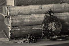 Antyka fob kieszeniowy zegarek z ?a?cuchem opiera na stercie stare ksi??ki Na drewnianym tle zdjęcia royalty free