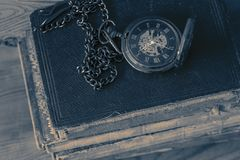 Antyka fob kieszeniowy zegarek z ?a?cuchem na stercie stare ksi??ki Na drewnianym tle fotografia royalty free