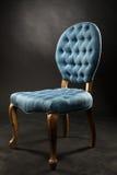 Antykwarski błękitny aksamitny krzesło blisko ciemnego pokoju Zdjęcia Stock
