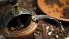 Antykwarski kawowy ostrzarz z kawowymi fasolami w zamazanym tle zbiory wideo