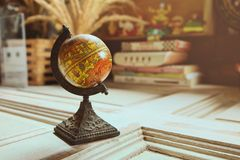 Antykwarski kula ziemska model na drewno stole z pomarańczowym światłem słonecznym, rocznika styl zdjęcia royalty free