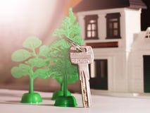 Antykwarski metalu klucz na kolor miniatury drewnianym domu Fotografia Stock