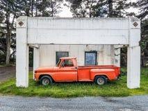 Antykwarski pomarańczowy pickup bagażnik parkujący pod budynkiem Zdjęcia Stock