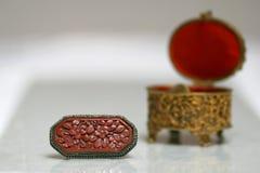 Antykwarski pudełka i broszki wciąż życie złota i czerwieni jewellery obraz royalty free