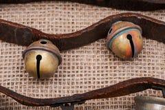 Antykwarski rocznik utlenia mosiężnych sanie dzwony na rzemiennej patce i burlap zdjęcie royalty free