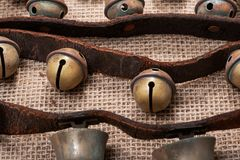 Antykwarski rocznik utlenia mosiężnych sanie dzwony na rzemiennej patce i burlap fotografia royalty free