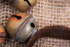 Antykwarski rocznik utlenia mosiężnych sanie dzwony na rzemiennej patce i burlap zdjęcia stock