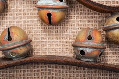 Antykwarski rocznik utlenia mosiężnych sanie dzwony na rzemiennej patce i burlap obraz stock