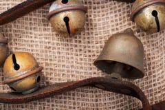 Antykwarski rocznik utlenia mosiężnych sanie dzwony na rzemiennej patce i burlap fotografia stock