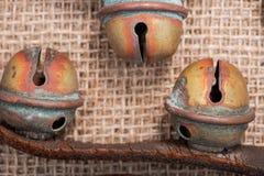 Antykwarski rocznik utlenia mosiężnych sanie dzwony na rzemiennej patce i burlap obrazy royalty free
