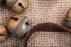 Antykwarski rocznik utlenia mosiężnych sanie dzwony na rzemiennej patce i burlap zdjęcia royalty free