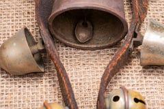 Antykwarski rocznik utlenia mosiężnych sanie dzwony na rzemiennej patce i burlap obraz royalty free