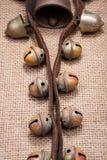 Antykwarski rocznik utlenia mosiężnych sanie dzwony na rzemiennej patce i burlap zdjęcie stock