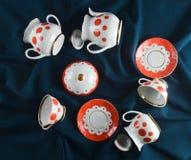 Antykwarski ustawiający naczynia na ciemnym barwionym sukiennym tablecloth Ceramiczny teapot, spodeczek, filiżanka fotografia royalty free