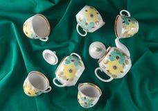 Antykwarski ustawiający naczynia na ciemnym barwionym sukiennym tablecloth Ceramiczny teapot, spodeczek, filiżanka Odgórny widok obraz stock
