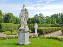 Antykwarskie statuy w kwiatu ogródzie Obraz Royalty Free