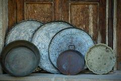 Antykwarskie tace i basenowy handmade żelazo i stal z obywatelów ornamentami na tle stary i wzorami, brąz, drewniany drzwi fotografia stock