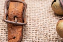 Antykwarskiego rocznika rzemienna patka z utlenia mosiężną klamrę od sanie dzwonów na burlap obrazy royalty free