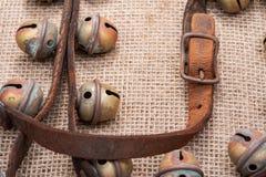 Antykwarskiego rocznika rzemienna patka z utlenia mosiężną klamrę od sanie dzwonów na burlap obraz stock