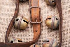 Antykwarskiego rocznika rzemienna patka z utlenia mosiężną klamrę od sanie dzwonów na burlap zdjęcie stock