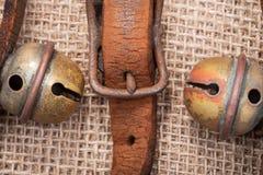 Antykwarskiego rocznika rzemienna patka z utlenia mosiężną klamrę od sanie dzwonów na burlap zdjęcia royalty free