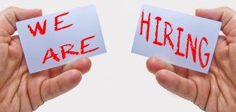 Anuncio de reclutamiento del trabajo representado por ?NOSOTROS ESTAMOS EMPLEANDO ?los textos en tarjetas en las manos del hombre fotografía de archivo libre de regalías