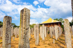 Anuradhapura Brazen Palace Stone Pillars Angled H. Stone pillars are all that remains of the ruins of the Brazen Palace or Lovamahapaya on a cloudy blue sky day Royalty Free Stock Photos