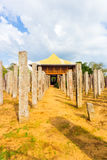 Anuradhapura Brazen Palace Stone Pillars Front V. Stone pillars of the ruins of Brazen Palace or Lovamahapaya lead into a modern structure on a cloudy blue sky Stock Image