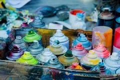 Använd ærosolsprutmålningsfärg i cans i låda royaltyfria foton