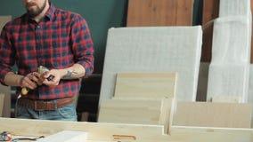 Använd en skruvmejsel i tillverkningen av wood produkter arkivfilmer