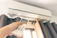 Använd fjärrkontrollen för att vända på luftkonditioneringsapparaten royaltyfri fotografi